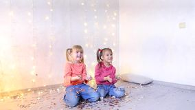 Two little girls posing on camera, children waving with hands and throw up confetti. Two little girls posing on camera for Christmas photos, children laugh stock footage