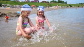 Two little girls pouring water on the beach. Children play, laugh, create splashes. Summer vacation at sea. Twins pour water on a hot summer day, laughter and stock footage