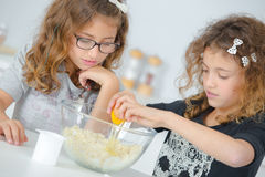Two little girls preparing cake mix Stock Image