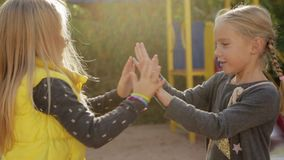 Two little girls preschoolers fooling around and playing patty-cake. On the playground stock footage