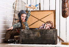 Two little girls pretending pilots in big chest Royalty Free Stock Images