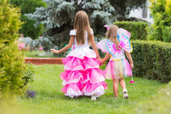 Two little girls, princess and fairy strolling through the garden. Two girls of four and six years of walking through the green garden Royalty Free Stock Images