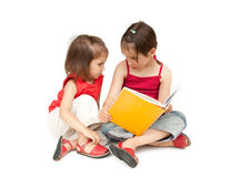 Two little girls reading a book Stock Image