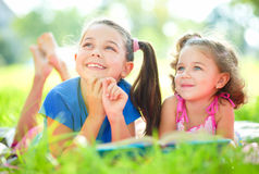 Two little girls are reading book. While laying on green grass, outdoor shoot Stock Photos