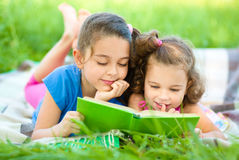 Two little girls are reading book. While laying on green grass, outdoor shoot Royalty Free Stock Photo