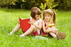 Two little girls reading a book on the nature and talking Stock Images