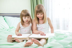 Two little girls reading book. Sitting on bed Royalty Free Stock Images