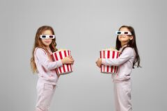 Two little girls in red-blue 3d glasses holding popcorn buckets