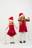 Two little girls in a red dress in caps Santa Claus Stock Images