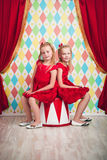 Two little girls in red dresses. In circus scenery Royalty Free Stock Images