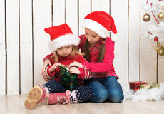 Two little girls in red hats sitting on the floor with gifts Stock Images
