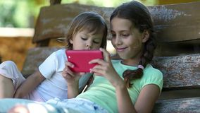 Two little girls with red smartphone sits on the swing bench stock video footage