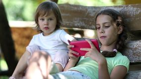 Two little girls with red smartphone sits on swing bench stock video footage
