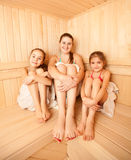 Two little girls relaxing in sauna with mother Stock Photography