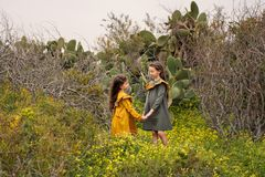 Two little girls in retro vintage dresses holding hands stand in cactuses and overgrown branches. Two little girls in retro vintage dresses holding hands and stock photo