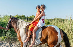 Two little girls riding horse in the summer in Ada Bojana, Monte Stock Photo
