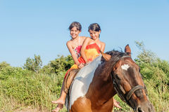 Two little girls riding horse in the summer in Ada Bojana, Monte Royalty Free Stock Images