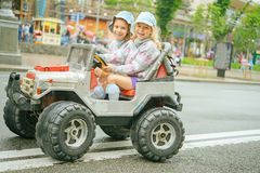 Two little girls riding toy car Stock Photo