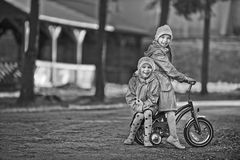 Two little girls riding toy cycle Royalty Free Stock Photo