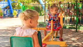 Two little girls rock on swing on play ground in tropical park stock video footage