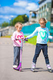 Two little girls roller skating and riding a Stock Images