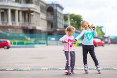 Two little girls roller skating and riding a Stock Photo