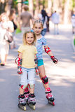 Two little girls rollerskating in the park Royalty Free Stock Images
