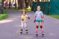 Two little girls rollerskating in the park Royalty Free Stock Photos