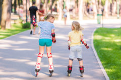 Two little girls rollerskating in the park Stock Photos
