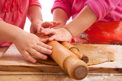 Two little girls with rolling pins baking Royalty Free Stock Image