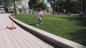 Two happy children running in summer park. Two little girls are running around the green grass in the center of the city. a walk of two sisters through the city stock video