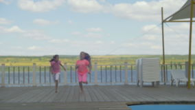 Two little girls running on a pier.  stock footage
