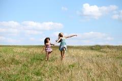 Two little girls running in summer field. Two Happy little girls running in summer field Stock Image