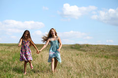Two little girls running in summer field. Two Happy little girls running in summer field Stock Photography