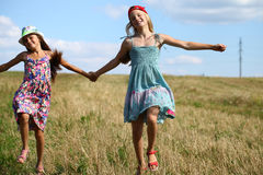 Two little girls running in summer field. Two Happy little girls running in summer field Royalty Free Stock Photos