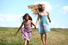Two little girls running in summer field. Two Happy little girls running in summer field Royalty Free Stock Photo