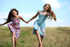 Two little girls running in summer field Stock Photos