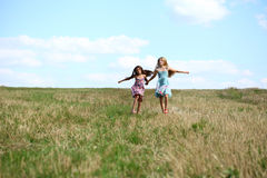 Two little girls running in summer field. Two Happy little girls running in summer field Royalty Free Stock Image