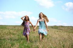 Two little girls running in summer field. Two Happy little girls running in summer field Royalty Free Stock Images