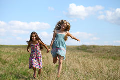 Two little girls running in summer field Royalty Free Stock Image