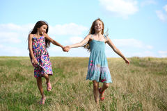 Two little girls running in summer field. Two Happy little girls running in summer field Royalty Free Stock Photography