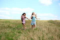 Two little girls running in summer field. Two Happy little girls running in summer field Stock Photo