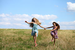 Two little girls running in summer field Stock Images
