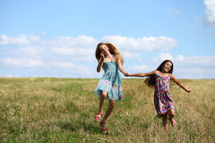 Two little girls running in summer field Royalty Free Stock Images
