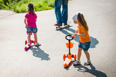 Two little girls on scooters. Two beautiful girls are standing on the scooter on the street Stock Images