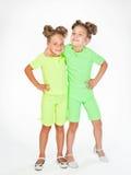 Two little girls in similar fancy garb Stock Photo