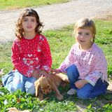 Two little girls sister friends golden retriever. Puppy dog outdoor park Royalty Free Stock Photography