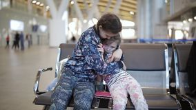 Two little girls sisters at the airport with a tablet put up. Little adorable girls in airport waiting for boarding playing with laptop stock video footage