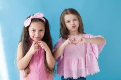 Two little girls are sisters girlfriends in a pink dress. Two little girls are sisters girlfriends pink dress royalty free stock images
