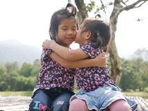 Free Two Little Girls, Sisters, Hugging And Kissing On A Bench In The Evening Sunlight - Sisters` Bond And Love Stock Photography - 194108592